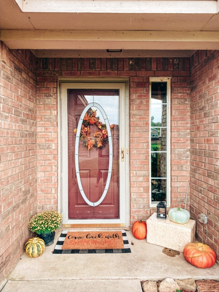 Affordable Fall Front Porch Decor by popular San Diego life and style blog, The Brunette and The Beach: image of a front porch decorated with a Walmart Harvest Collection Orange Pumpkin & Berry Mix Wreath, Amazon  Outdoor Buffalo Check Door Mat, Kirkland's Come Back With Pumpkin Spice Doormat, pumpkins, and Target Spritz Decorative Bale of Hay.