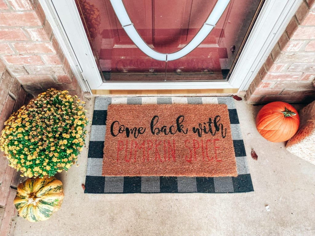 Affordable Fall Front Porch Decor | Affordable Fall Front Porch Decor by popular San Diego life and style blog, The Brunette and The Beach: image of a front porch decorated with a Walmart Harvest Collection Orange Pumpkin & Berry Mix Wreath, Amazon  Outdoor Buffalo Check Door Mat, Kirkland's Come Back With Pumpkin Spice Doormat, pumpkins, and Target Spritz Decorative Bale of Hay.