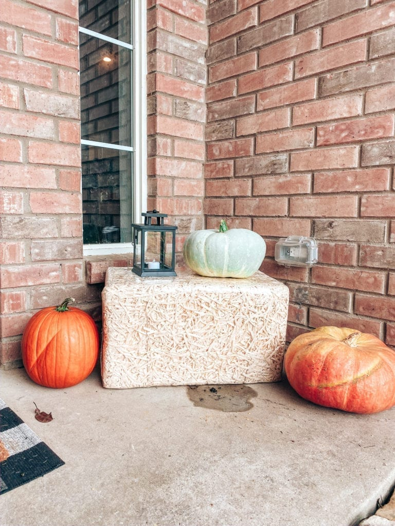 fall outdoor decor | Affordable Fall Front Porch Decor by popular San Diego life and style blog, The Brunette and The Beach: image of a front porch decorated with a Walmart Harvest Collection Orange Pumpkin & Berry Mix Wreath, Amazon  Outdoor Buffalo Check Door Mat, Kirkland's Come Back With Pumpkin Spice Doormat, pumpkins, and Target Spritz Decorative Bale of Hay.