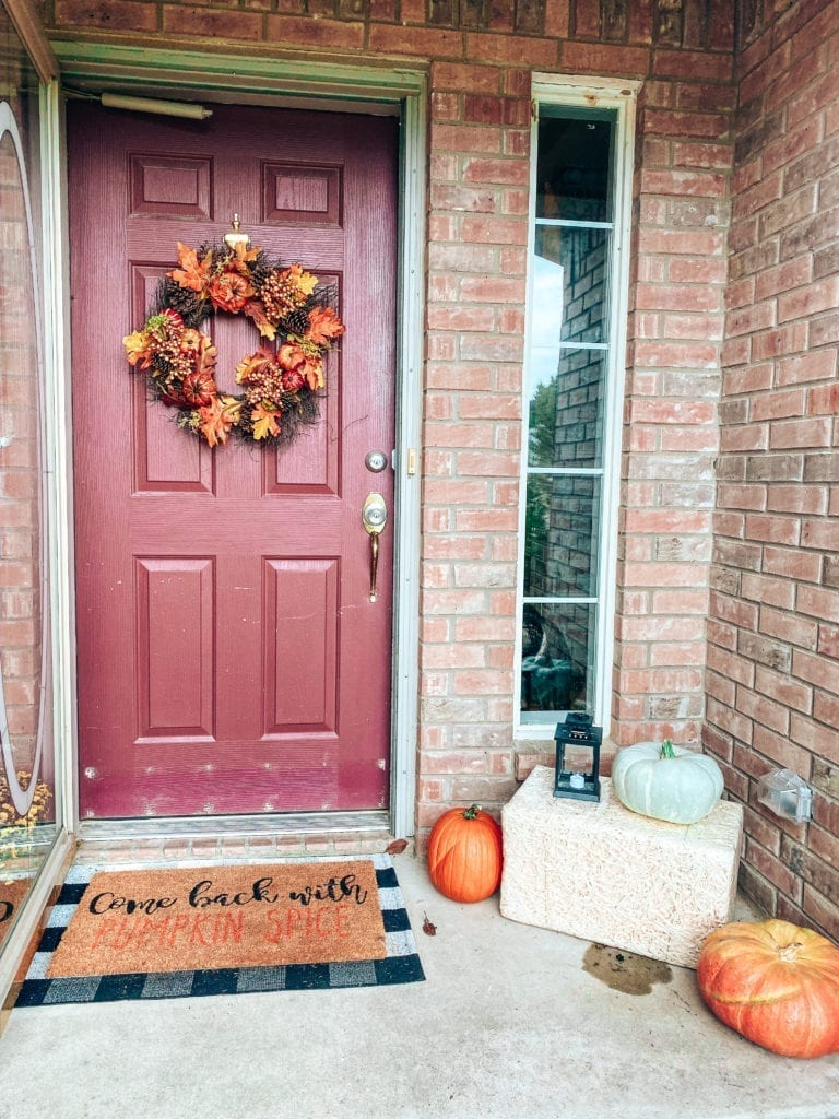 fall front porch | Affordable Fall Front Porch Decor by popular San Diego life and style blog, The Brunette and The Beach: image of a front porch decorated with a Walmart Harvest Collection Orange Pumpkin & Berry Mix Wreath, Amazon  Outdoor Buffalo Check Door Mat, Kirkland's Come Back With Pumpkin Spice Doormat, pumpkins, and Target Spritz Decorative Bale of Hay.
