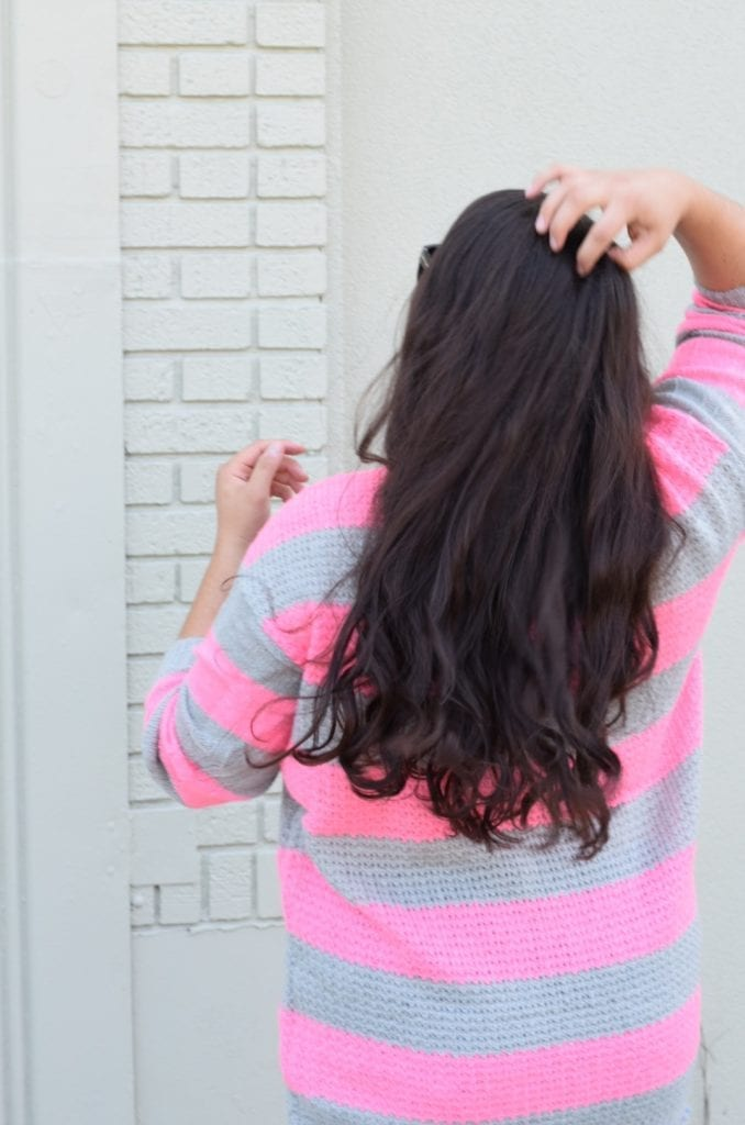 Keeping Your Hair Healthy Year Round | How to Keep Your Hair Healthy Year Round by popular San Diego beauty blog, The Brunette and the Beach: image of a woman running her fingers through her long brunette hair.